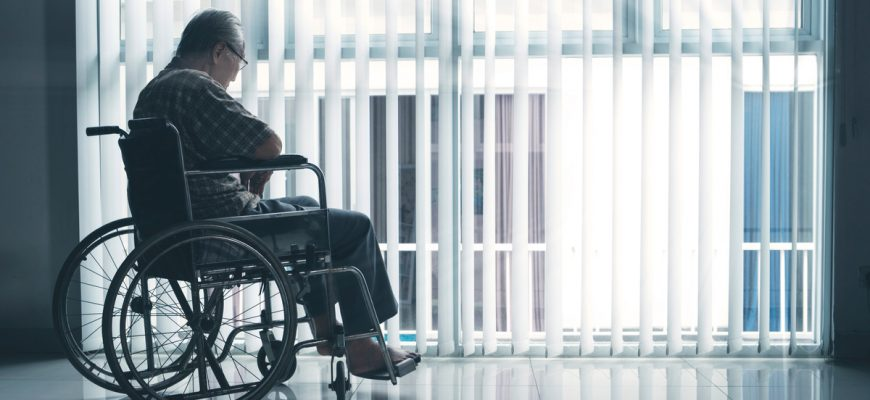 Lonely senior resident in assisted living facility looks out the window solemnly as he sits in his wheelchair.