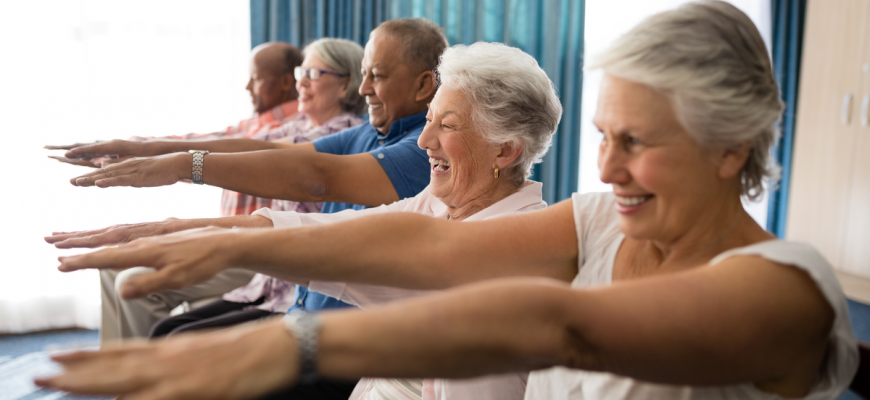 Seniors doing exercises at an assisted living home.